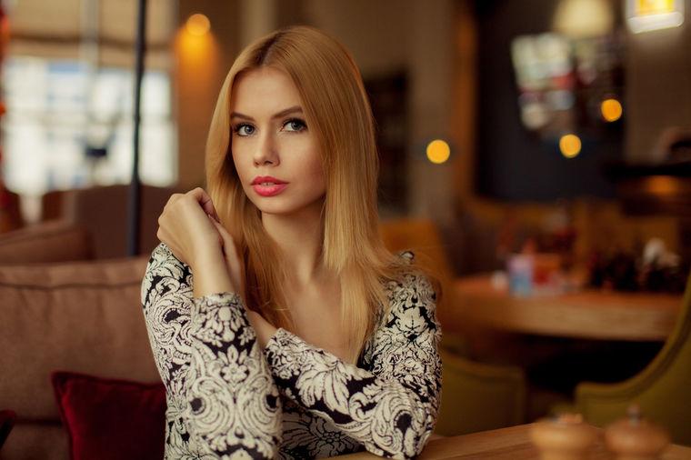 Devojka sedi u kafiću